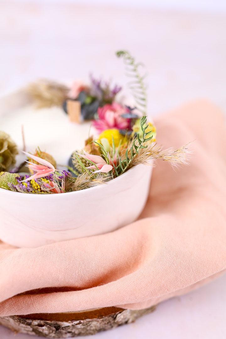 Photo d'une bougie à base de cire de soja et de fleurs séchées