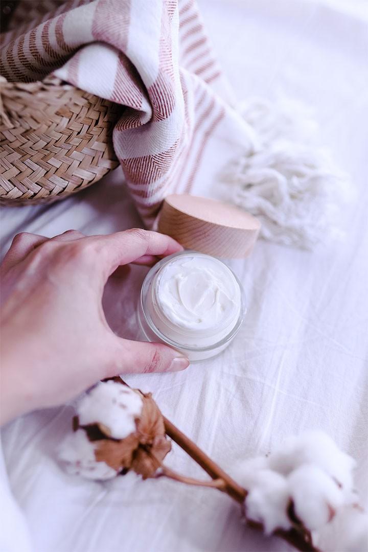 pot de crème visage maison à l'aloe vera dans les mains d'une femme